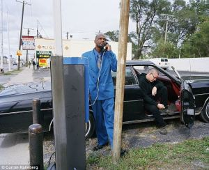 A man in a blue suit talks on a payphone while another man sits inside a black car in Detroit, Michigan